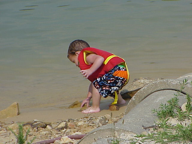 A young visitor playing near the water at Laurel River Lake's beach, Harlan, Ky.