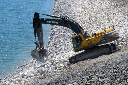 A contractor works on the rip rap on the Wolf Creek Dam embankment in April 2013