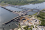 This aerial photo of the Kentucky Lock Addition project taken April 26, 2013 in Grand Rivers, Ky., shows construction of a new 1200-foot lock landward of the existing 600-foot lock and the relocated highway and railroad bridges downstream of the dam. The upstream-bound split barge tow will be able to lock through as a single tow when the new lock is completed by the U.S. Army Corps of Engineers Nashville District in partnership with the Tennessee Valley Authority. (USACE Photo)