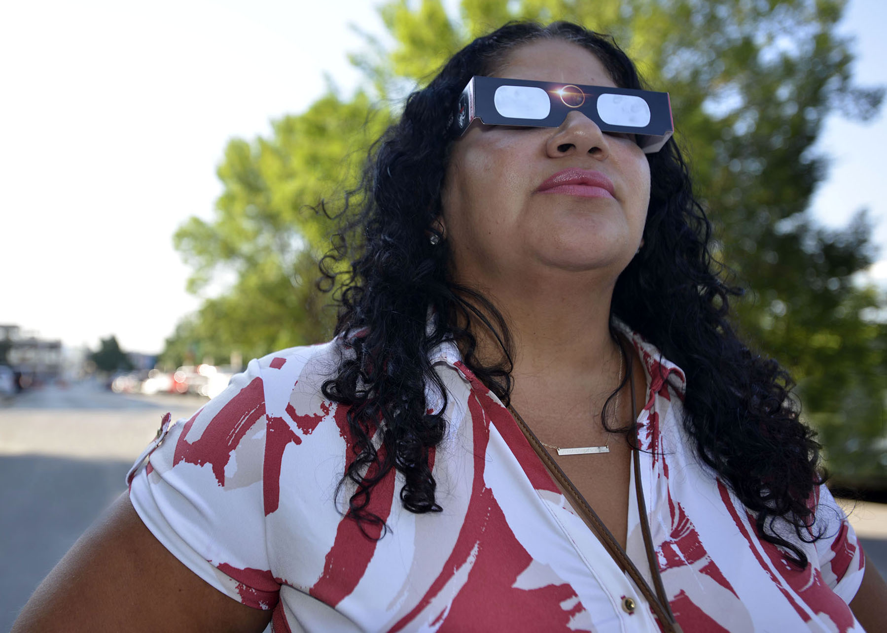 Woman wears eclipse safety glasses