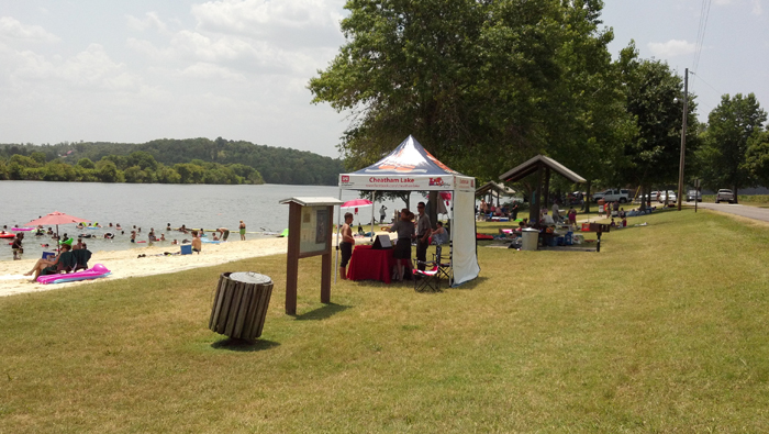 Chetaham park rangers hand out water safety information at a beach at Cheatham Lake, Ashland City, Tenn.