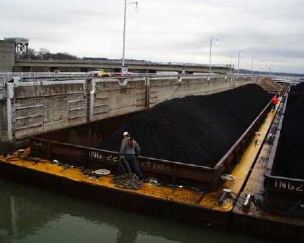 A worker prepares to move the barges through the lock as the water has almost filled it.