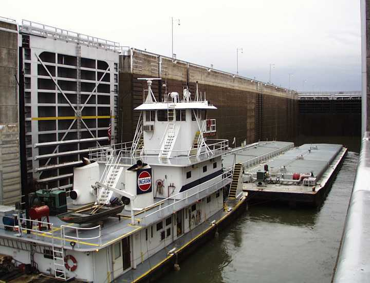 The tugboat pushes chemical barges filled with benzene into the lock.