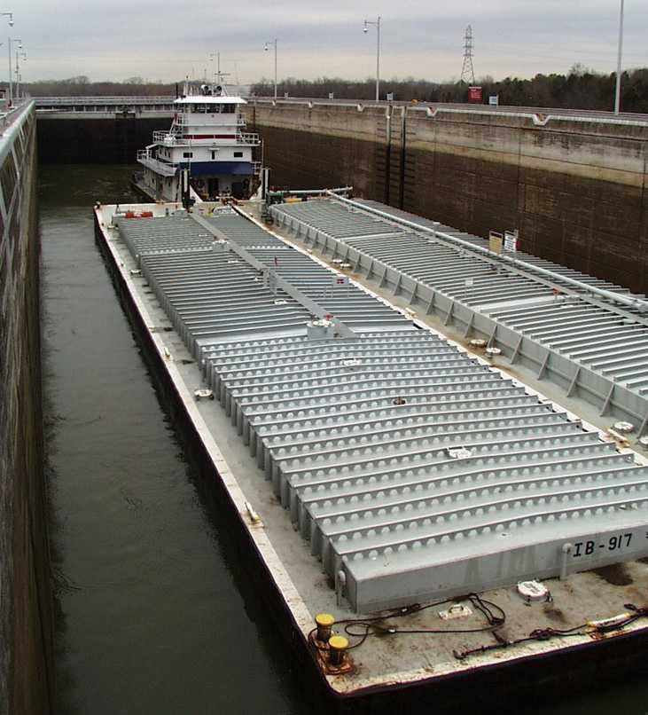 The lock fills with water, raising the tugboat and chemical barges.