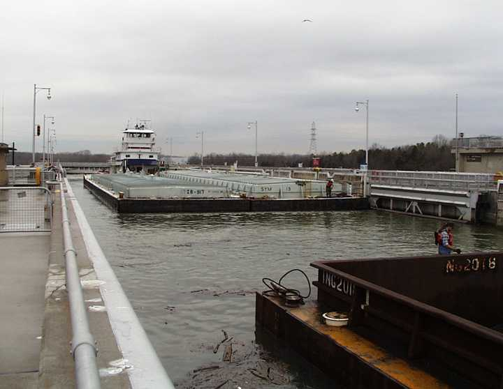 The tugboat slowly pushes the chemical barges toward the coal barges that are tied outside of the lock in the lake.